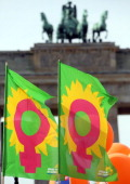 Flags with the female gender sign wave in front of the Brandenburg Gate during the 'Equal Pay Day' demonstration on March 21 2014 in Berlin Germany...