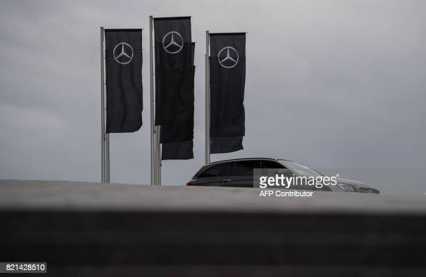 TOPSHOT Flags with the logo of German car brand MercedesBenz by car maker Daimler AG are pictured on July 24 2017 in Stuttgart southern Germany...