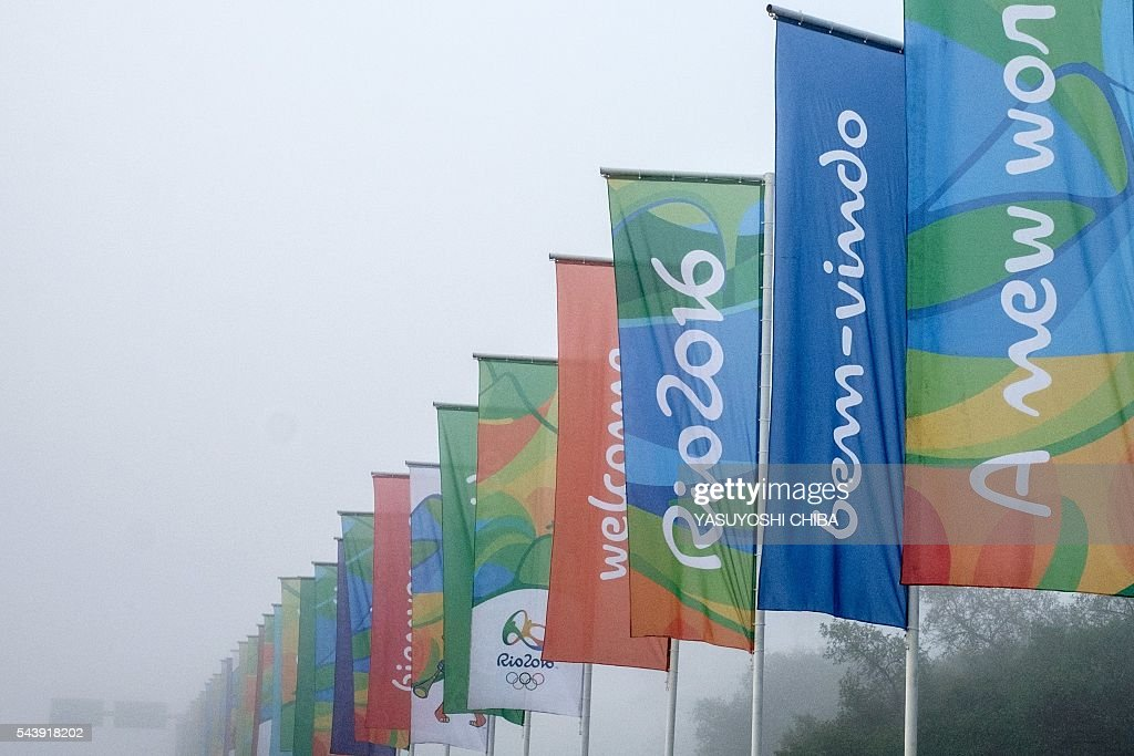 Flags with the logo of Rio 2016 Olympic and Paralympic Games among others reading 'Welcome' in different languages are view near Antonio Carlos Jobim (Galeao) International Airport in Rio de Janeiro, Brazil, on June 30, 2016. / AFP / YASUYOSHI