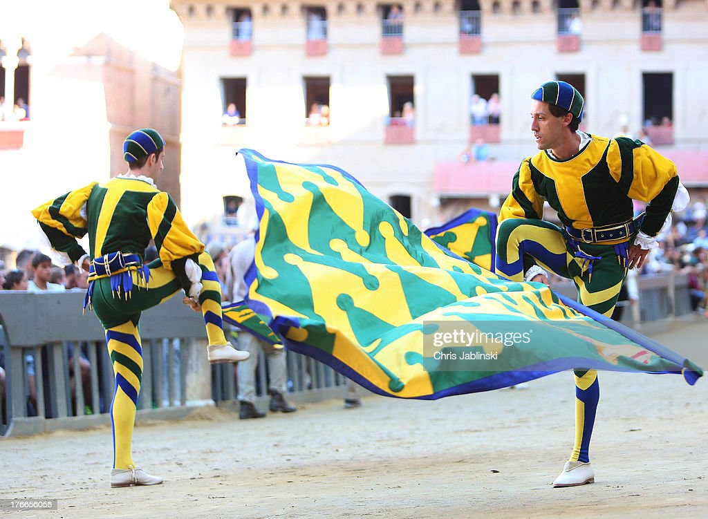 Flag-swingers of the Contrada del Bruco act at the Piazza del Campo before the annual Palio dell'Assunta horse-race on August 16, 2013 in Siena, Italy. The Palio races in Siena, in which riders representing city districts compete,and takes place twice a year in the summer in a tradition that dates back to 1656.
