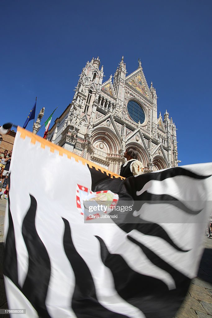 Flag-swingers of the Contrada della Lupa act in front of the dome in a procession that takes place before the annual Palio dell'Assunta horse-race on August 16, 2013 in Siena, Italy. The Palio races in Siena, in which riders representing city districts compete,and takes place twice a year in the summer in a tradition that dates back to 1656.