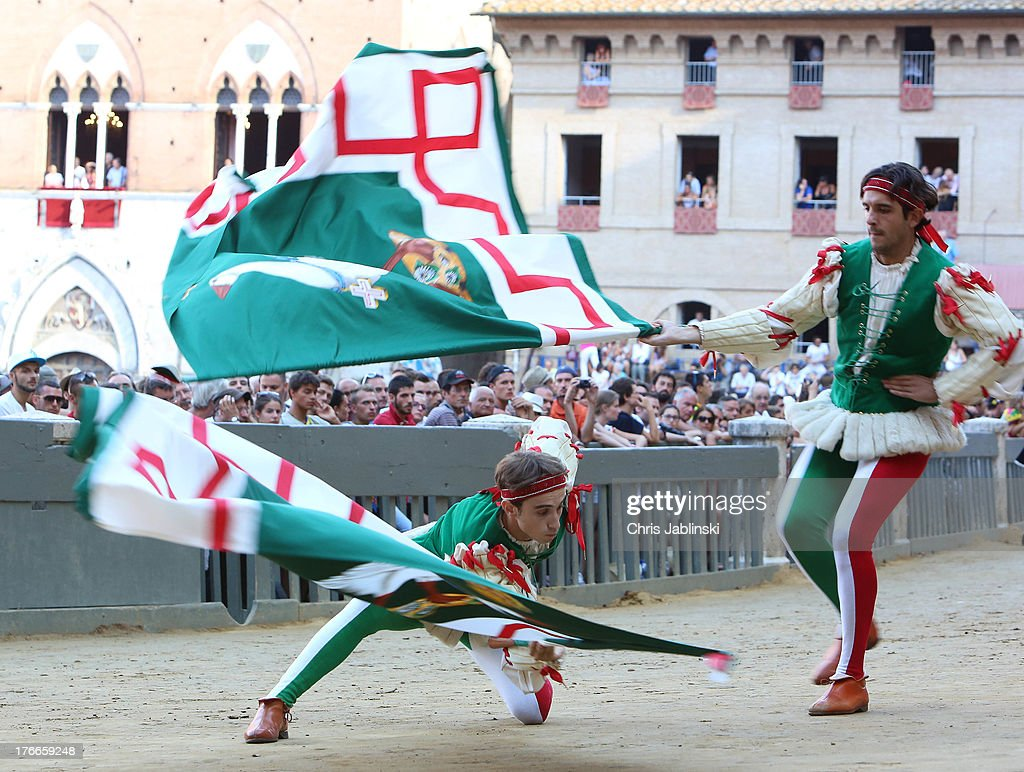 Flag-swingers of the Contrada dell`Oca act in a procession that takes place on the Piazza del Campo before the annual Palio dell'Assunta horse-race on August 16, 2013 in Siena, Italy. The Palio races in Siena, in which riders representing city districts compete,and takes place twice a year in the summer in a tradition that dates back to 1656.