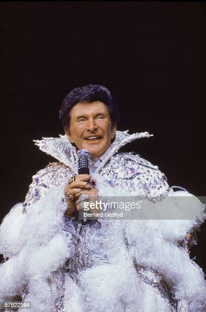 Flamboyant American piano player and entertainer Liberace sings into a microphone as he wears an ostentatious feather and rhinestone outfit during a...