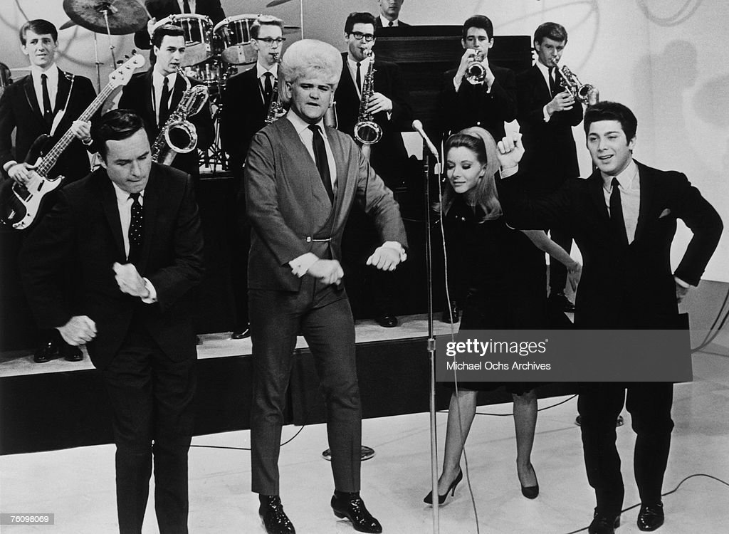 Flamboyant soul singer Wayne Cochran (second from left) performs on the Mike Douglas Show while host Mike Douglas (left), ventriloquist Shari Lewis (second from right), and singer Paul Anka (right) dance along circa the mid-1960s in Philadelphia, Pennsylvania.