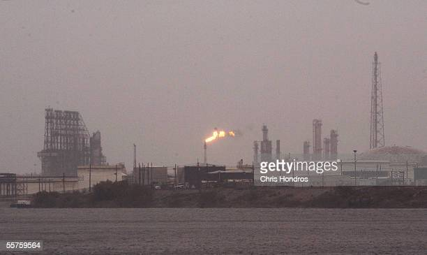 A flame from a petroleum refinery shines through the gloom at the Port of Beaumont as Hurricane Rita approaches September 23 2005 in Beaumont Texas...