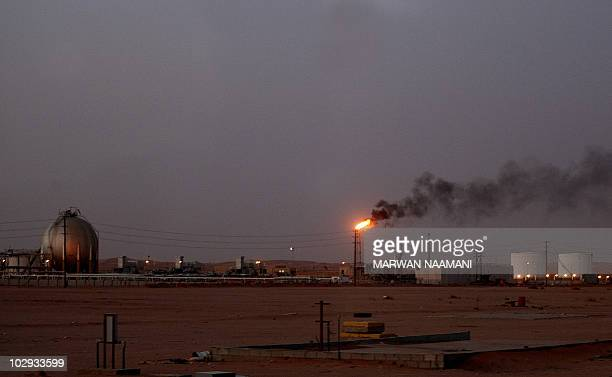 A flame from a Saudi Aramco oil installation known as 'Pump 3' burns brightly during sunset in the Saudi Arabian desert near the oilrich area...