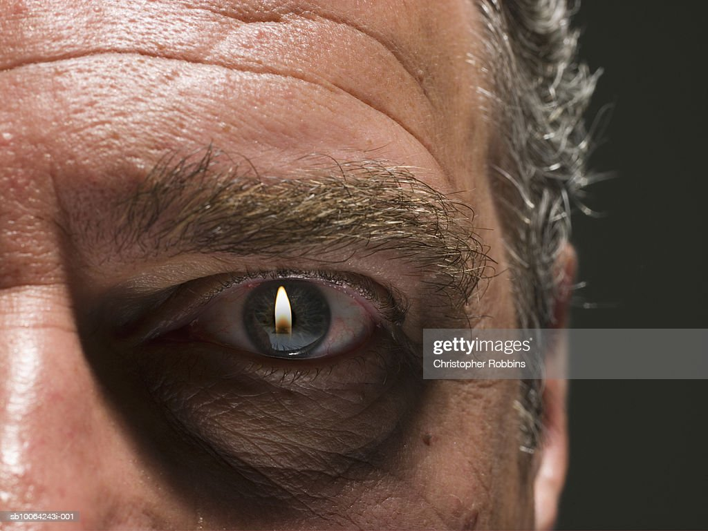 Flame projected in eye of senior man, close-up : Stock Photo