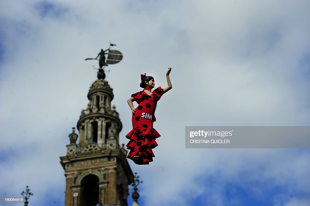 A flamenco dancer doll hangs in front of Sevilla's Cathedral to announce the SIMOF (International Flamenco Fashion Show) on January 26, 2013 in Sevilla. The SIMOF will be held from January 31 to February 3, in Sevilla .AFP PHOTO/ CRISTINA QUICLER