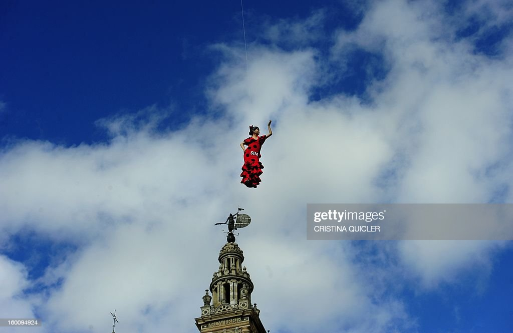 A flamenco dancer doll hangs in front of Sevilla's Cathedral to announce the SIMOF (International Flamenco Fashion Show) on January 26, 2013 in Sevilla