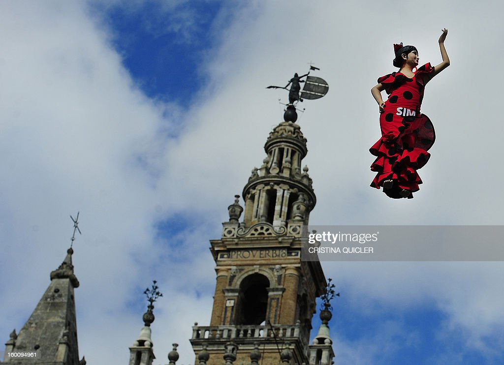 A flamenco dancer doll hangs in front of Sevilla's Cathedral to announce the SIMOF (International Flamenco Fashion Show) on January 26, 2013 in Sevilla. The SIMOF will be held from January 31 to February 3, in Sevilla .