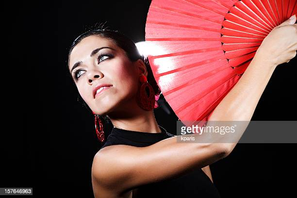 Flamenco dancer with red hand fan looking into the distance