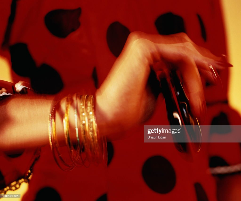 Flamenco dancer's hand holding castanets,red dress behind,blurred : Stock Photo