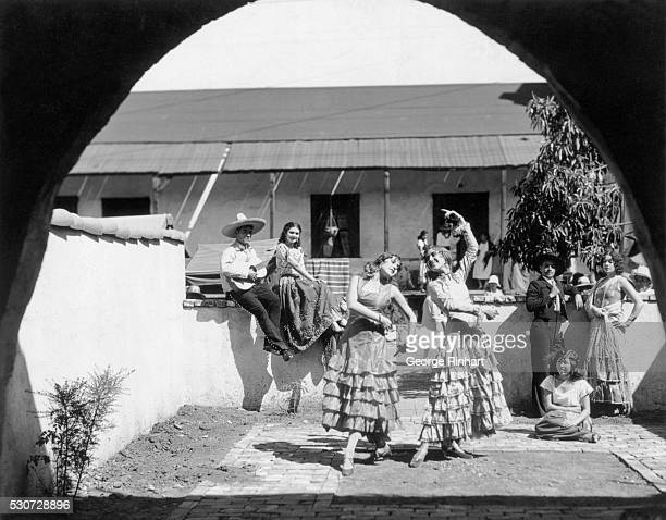 Flamenco dancers performing in sunny courtyard with guitar player Undated photograph