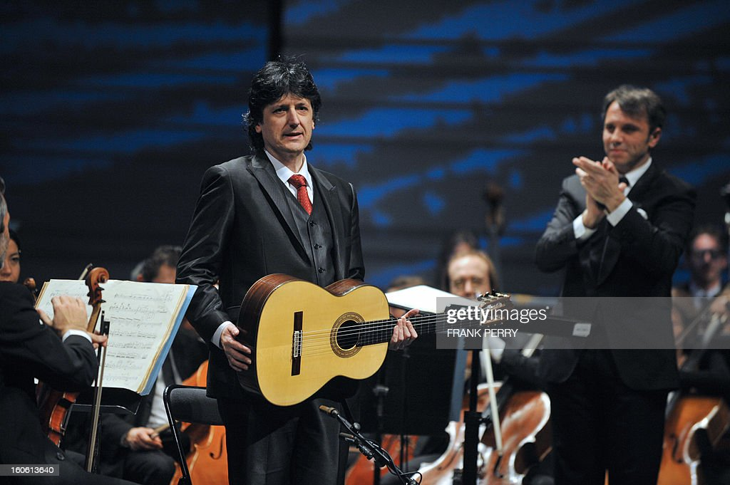 Flamenco guitarist Juan Manuel Canizares of Spain is applauded after performing the Aranjuez Concerto with the Lamoureux orchestra directed by French conductor Fayçal Karoui (R) on February 3, 2013, as part of the 'Folle Journee' music festival at the Cite des Congres in Nantes, western France. AFP PHOTO FRANK PERRY
