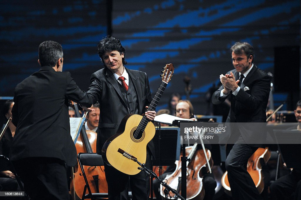 Flamenco guitarist Juan Manuel Canizares (C) of Spain is applauded after performing the Aranjuez Concerto with the Lamoureux orchestra directed by French conductor Fayçal Karoui (R) on February 3, 2013, as part of the 'Folle Journee' music festival at the Cite des Congres in Nantes, western France.