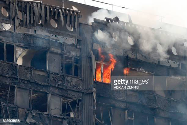 Flames and smoke continue to engulf Grenfell Tower a residential block of flats in west London on June 14 as firefighters continue to control a fire...
