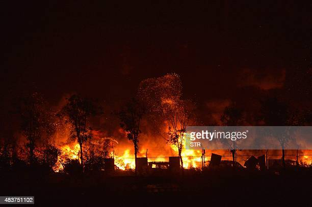 Flames and smoke rise from the site of a series of explosions in Tianjin early on August 13 2015 A series of massive explosions at a warehouse in the...