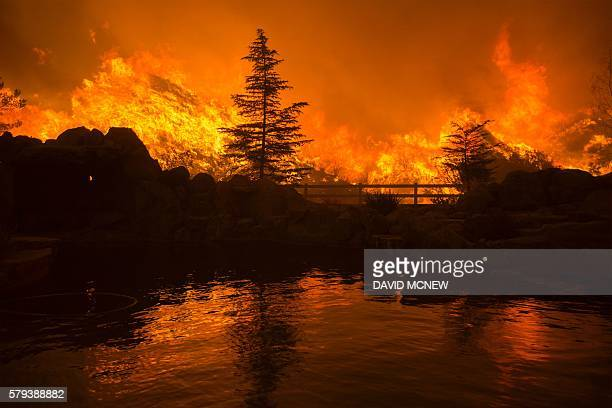 TOPSHOT Flames are reflected in a backyard swimming pool at the Sand Fire on July 23 2016 near Santa Clarita California Fueled by temperatures...