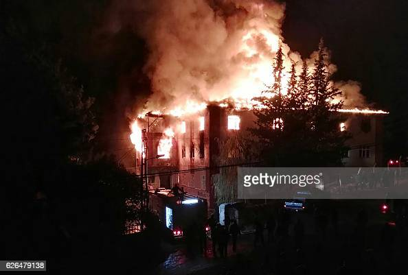 Flames are seen as firefighters try to control a fire at a school in Adana southern Turkey on November 29 2016 Twelve people most of them children...