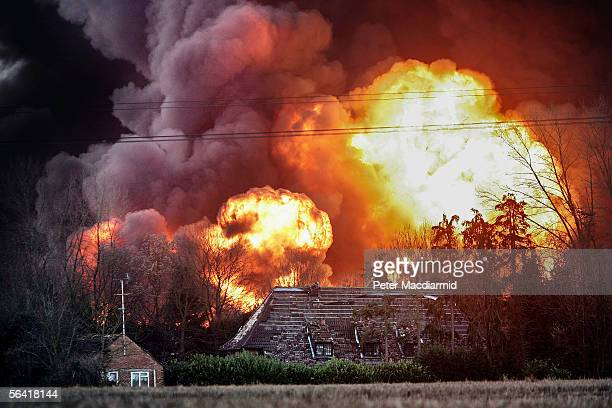 Flames are seen behind a house next to the Buncefield oil depot on December 12 2005 in Hemel Hempstead England Fire officers continue to tackle the...