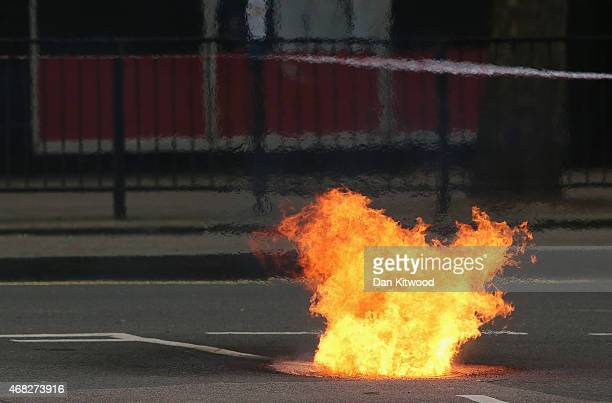 Flames are seen escaping from a manhole cover as fire crews tend to an underground cable fire at Lincoln's Inn Fields in on April 1 2015 in London...
