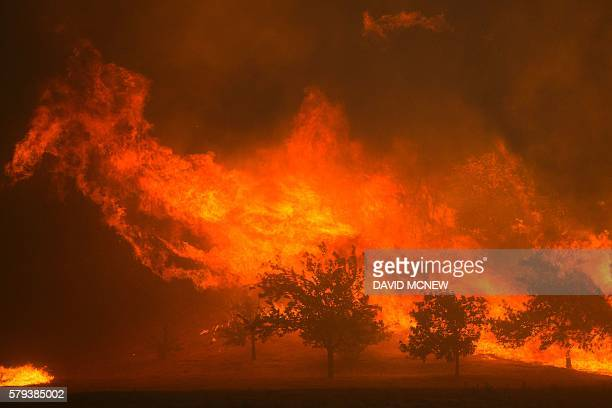 TOPSHOT Flames blown by strong winds close in on homes at the Sand Fire on July 23 2016 near Santa Clarita California Fueled by temperatures reaching...