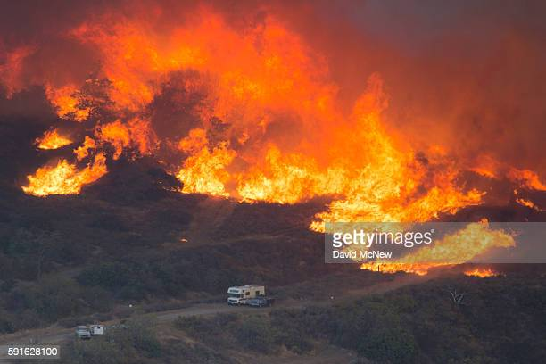 Flames close in on cars parked along a country road at the Blue Cut Fire on August 17 2016 near Wrightwood California An unknown number of homes and...
