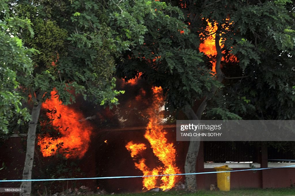 Flames come out following an explosion after authority found a homemate bomb in front of the National Assembly building in Phnom Penh on September 13, 2013. Cambodia's opposition said on September 12, that it had filed a lawsuit against the kingdom's poll authorities over strongman Prime Minister Hun Sen's disputed election win. AFP PHOTO / TANG CHHIN SOTHY