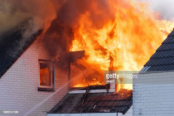 Flames coming out of white brick wall house on fire