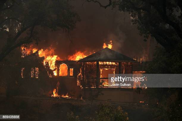 Flames consume a home as an out of control wildfire move through the area on October 9 2017 in Glen Ellen California Tens of thousands of acres and...