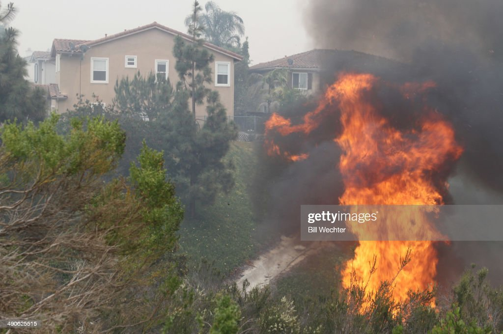 Flames flare up behind houses on Mimosa Drive May 14 2014 in Carlsbad California Thirty homes have burned in the fastmoving Carlsbad blaze fueled by...