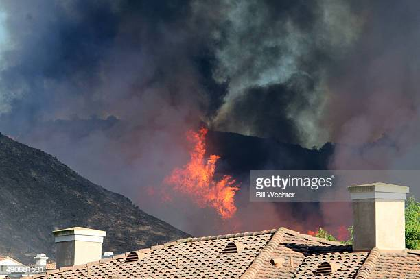 Flames flare up on a hillside behind an apartment complex near California State University at San Marcos May 14 2014 in San Marcos California About...