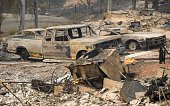 Flames from an open gas line burn next to destroyed vehicles parked in the driveway of a home charred by the Valley fire in Middletown California on...