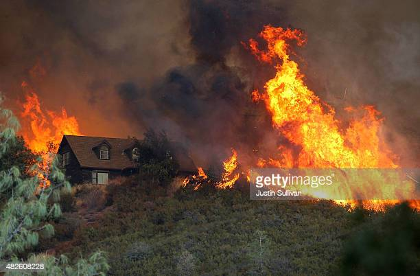 Flames from the Rocky Fire approach a house on July 31 2015 in Lower Lake California Over 900 firefighters are battling the Rocky Fire that erupted...