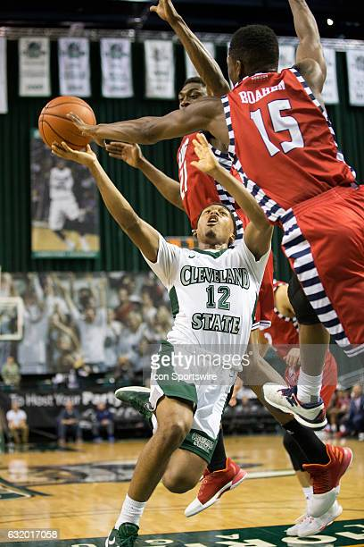 Flames G Godwin Boahen blocks the shot of Cleveland State Vikings G Kasheem Thomas as UIC Flames F/C Tai Odiase also defends during the final minute...