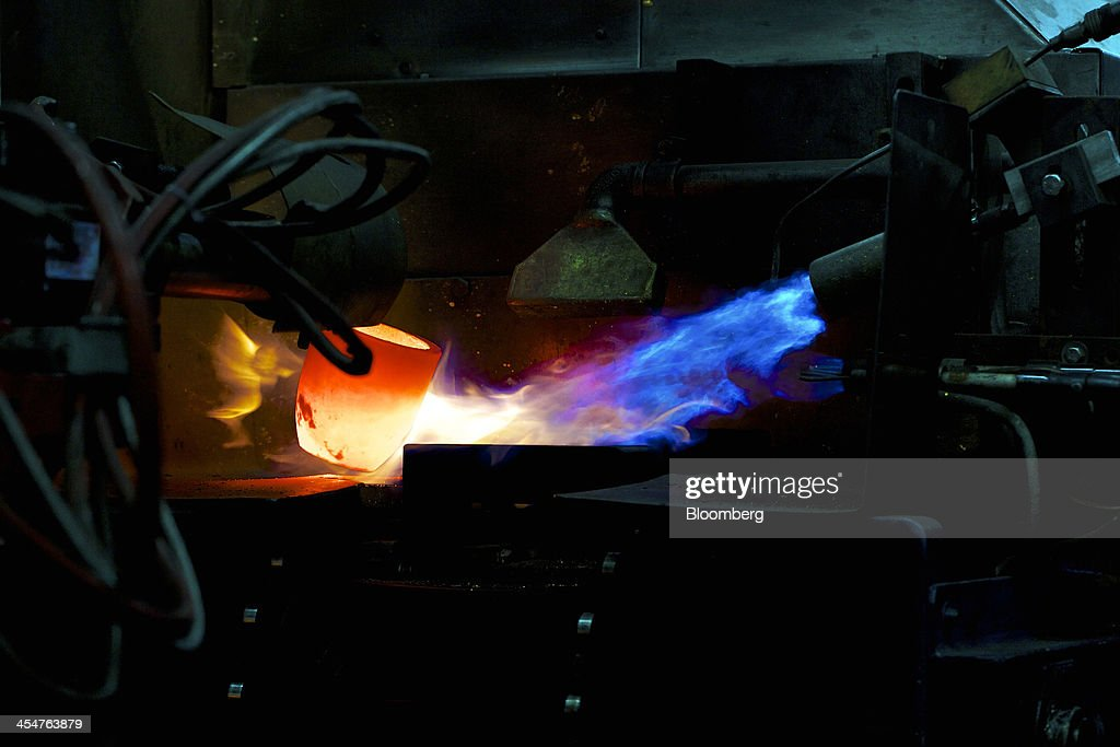 Flames heat a mould before molten gold is poured into it during the semiautomated gold bar manufacturing process at a precious metal refinery near...
