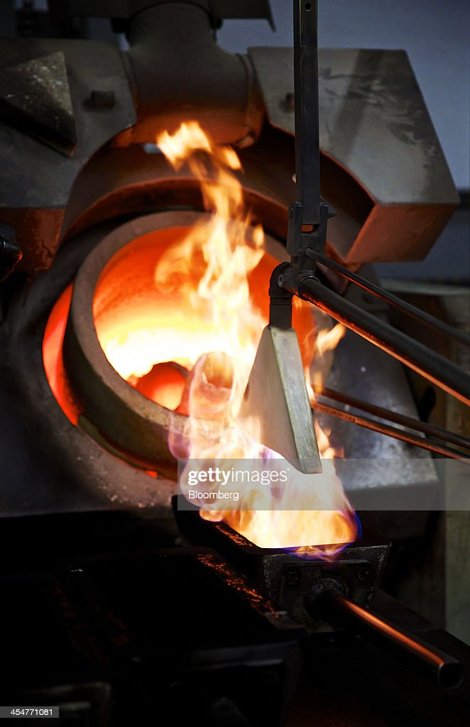 Flames heat a one kilogram mould before molten silver is cast during the semiautomated gold and silver bar manufacturing process at a precious metal...