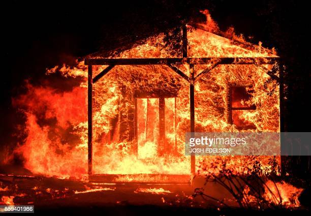 TOPSHOT Flames overtake a structure as nearby homes burn in the Napa wine region in California on October 9 as multiple winddriven fires continue to...