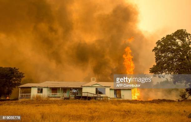 Flames rise above a home in Mariposa California on July 19 2017 The Detwiler fire which has burned more than 45000 acres and destroyed eight...