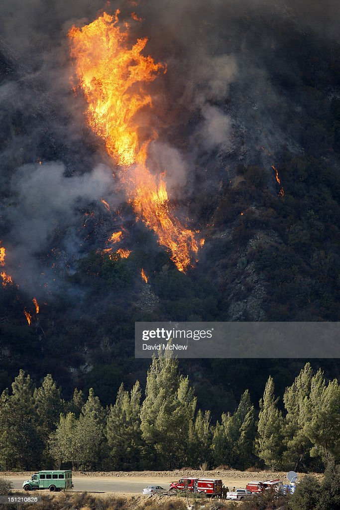 Flames rise behind firefighters as the Williams fire continues to spread in the Angeles National Forest on September 3, 2012 north of Glendora, California. The fire began late September 2, putting an early end to Labor Day weekend camping and hiking for vacationers, who were evacuated from the area as it spread to more than 4,000 acres in size. Three hundred to 400 firefighters are on the ground, with more expected to arrive soon, and at least six air tankers and eight helicopters have been called in.