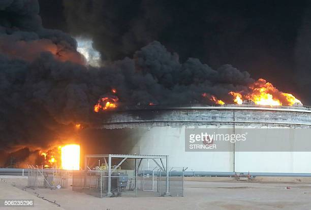 Flames rise from a storage tank filled with crude oil at an oil facility in northern Libya's Ras Lanouf region after it was set ablaze following...