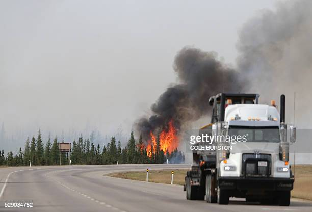 Flames rise off Highway 63 on May 7 2016 outside Fort McMurray where raging forest fires have forced more than 88000 from their homes A ferocious...