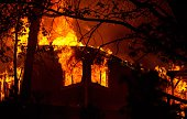 Flames shoot out of the windows of a burning house during the Valley fire in Seigler Springs California on September 13 2015 The governor of...