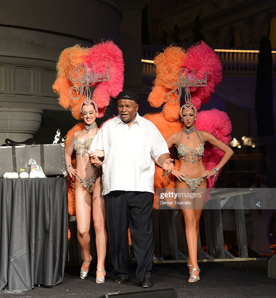 Flamingo Las Vegas headliner George Wallace (C) and showgirls from Bally's Las Vegas headliner Jubilee during the closing night party for IPW 2013 at the Garden for the Gods pool at Caesars Palace on June 12, 2013 in Las Vegas, Nevada.