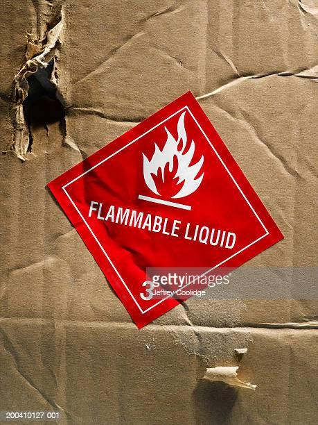 Flammable liquid warning label on torn box, close-up