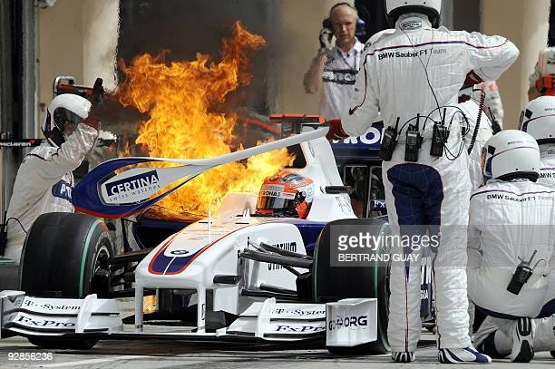 Flams escape from BMW Sauber's Polish driver Robert Kubica's car as he refuels in the pits of the Sakhir racetrack during the qualifying session of...