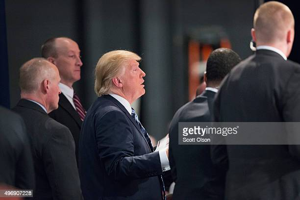 Flanked by a members of his Secret Service detail Republican presidential candidate Donald Trump greets guests during a campaign stop at Iowa Central...