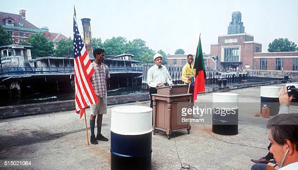 Flanked by an American and a black power flag Dr Thomas Matthew explains to the press on Ellis Island on July 25 1970 that he and about 40 other...
