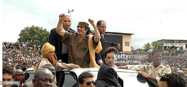 Flanked by bodyguards Libyan leader Moamer Kadhafi clinches his fists in victory as he is driven in a car on his way to deliver a speech in front of...