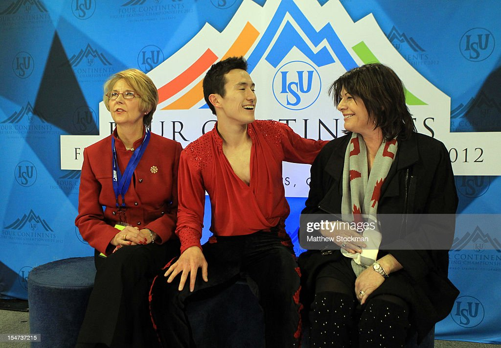 Flanked by his coaches Christy Krall and Kathy Johnson, Patrick Chan of Canada watches his scores in the Kiss & Cry after the Men's Free Skate during the ISU Four Continents Figure Skating Championships at World Arena on February 10, 2012 in Colorado Springs, Colorado.